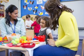 two preschool teachers talking to one student at a table with kitchen-themed toys